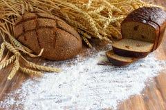 麦子的面包和耳朵在木背景的 图库摄影