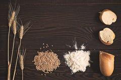 麦子耳朵、五谷、面粉和切的面包在一张黑暗的木桌上 免版税库存照片