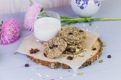 麦甜饼用干果子,种子,蔓越桔 在与一杯的木灰色背景新鲜的温暖的牛奶 舒适静物画 免版税库存图片