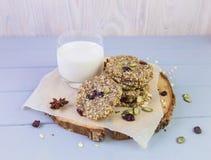 麦甜饼用干果子,种子,蔓越桔 在与一杯的木灰色背景新鲜的温暖的牛奶 舒适静物画 库存照片