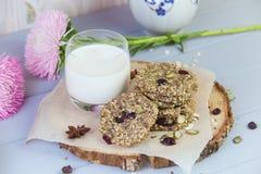 麦甜饼用干果子,种子,蔓越桔 在与一杯的木灰色背景新鲜的温暖的牛奶 舒适静物画 库存图片