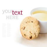 麦甜饼用葡萄干和杯子在白色backg的绿茶 免版税库存照片