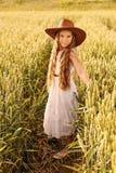 麦田的一个女孩在牛仔帽 库存图片