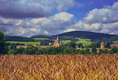 麦田的在村庄,伯根地教会 免版税库存照片