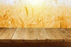 麦田背景和倒空木甲板桌 图库摄影
