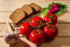 黑麦面包、萝卜、蕃茄、葱、绿色、大蒜草本和香料在木背景 库存照片