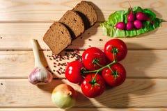 黑麦面包、萝卜、蕃茄、葱、绿色、大蒜草本和香料在木背景 免版税库存照片