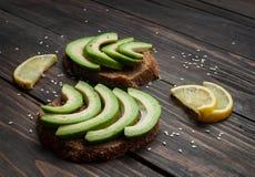 黑麦面包三明治用鲕梨和柠檬在木头 免版税库存照片