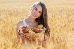 黑麦领域的女孩与小圆面包和卷篮子  图库摄影