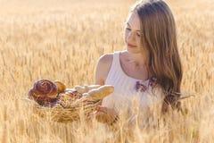 黑麦领域的青少年的女孩与小圆面包篮子  免版税库存照片