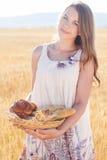 黑麦领域的青少年的女孩与小圆面包篮子  库存照片