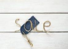 麻线题字销售在我的手,价牌上在牛仔布 库存照片