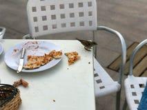 麻雀的一只小的饥饿的鸟吃从访客` s板材的食物在一个开放夏天咖啡馆的桌上在街道上 免版税库存照片