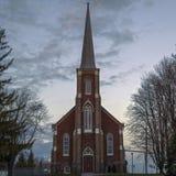 黄昏的一个红砖尖顶教会 免版税库存照片