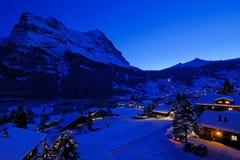 黄昏的格林德瓦村庄与Mt 埃格尔峰顶在背景中,积雪的风景在冬天,瑞士 免版税库存照片
