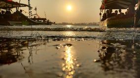 黄昏,当在一个浪漫海滩盐水湖边缘的太阳落山,当看小船时的阴影 图库摄影