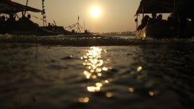 黄昏,当在一个浪漫海滩盐水湖边缘的太阳落山,当看小船时的阴影 免版税库存照片