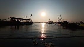 黄昏,当在一个浪漫海滩盐水湖边缘的太阳落山,当看小船时的阴影 库存图片