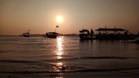 黄昏,当在一个浪漫海滩盐水湖边缘的太阳落山,当看小船时的阴影 库存照片