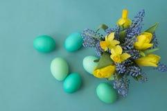黄水仙、郁金香和穆斯卡里花束  复活节 复活节彩蛋是蓝色和绿松石 免版税图库摄影