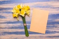黄水仙和纸片花束在木背景的 春天黄色花 图库摄影
