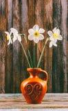 黄水仙花束的静物画在木葡萄酒难看的东西背景的一个老陶瓷水罐开花 免版税库存照片