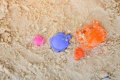 黄沙桶和蓝色铁锹儿童` s使在沙子玩具的玩具靠岸在海滩,孩子的活动的儿童沙盒的 免版税库存图片