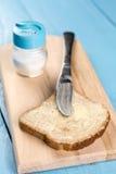 黄油传播在面包和服务在一个木板 免版税图库摄影
