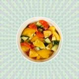 黄瓜和蕃茄菜沙拉在一个白色杯子在色的背景 免版税库存照片