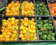 黄色不同的胡椒和绿色在箱子在超级市场 库存图片