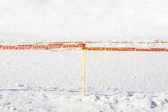 黄色中止磁带被围拢的结冰的冰孔 免版税库存图片