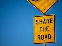 黄色份额在自行车道的路标 免版税库存照片