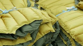 黄色冬天夹克一起被栓在服装工厂仓库 裁缝概念 股票录像