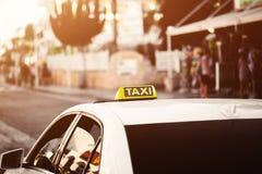 黄色出租汽车标志 在街道上的出租汽车汽车在城市 橙黄色温暖的定调子的bokeh背景 库存图片