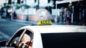 黄色出租汽车标志 在街道上的出租汽车汽车在城市 蓝色冷的定调子的bokeh背景 横幅大小 免版税库存照片