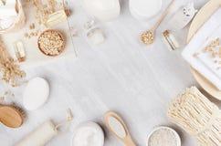 黄色化妆用品上油,燕麦粥flackes和白色奶油,在米黄木背景,拷贝空间,顶视图的浴自然辅助部件 免版税库存图片