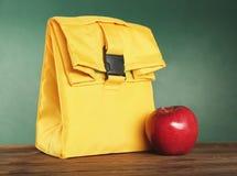 黄色午餐袋子和开胃红色苹果 库存照片