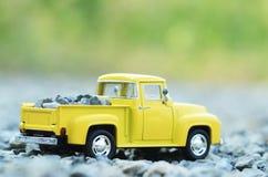 黄色卡车玩具有绿色bokeh轻的背景 库存照片