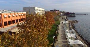 黄色叶子和一家夏天餐馆的白色帐篷秋天堤防的在波摩莱,保加利亚 免版税库存图片
