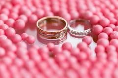 黄色和人造白金与金刚石的婚戒 桃红色球和泡影背景 仪式的原始的盘子  免版税库存图片