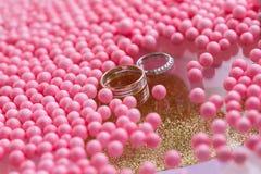 黄色和人造白金与金刚石的婚戒 桃红色球和泡影背景 仪式的原始的盘子  免版税库存照片
