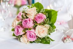 黄色和桃红色玫瑰美丽的花束在装饰的桌上的 免版税库存照片