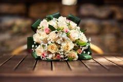黄色和玫瑰色玫瑰美妙地装饰的婚姻的花束在木桌上 库存图片