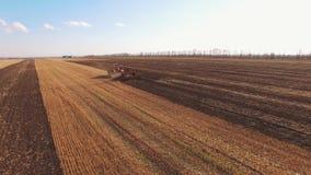 黄色和红色拖拉机耕领域空中电影 股票录像