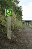 黄色和绿色步行者在一条狭窄的轨道只签字 库存图片