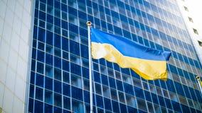 黄色和蓝色乌克兰旗子的图象反对现代营业所大厦的 免版税库存图片