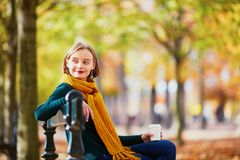 黄色围巾的愉快的女孩走在秋天公园的 图库摄影