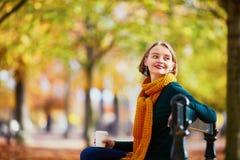 黄色围巾的愉快的女孩走在秋天公园的 免版税库存图片