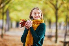 黄色围巾的愉快的女孩走在秋天公园的 库存照片