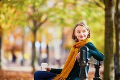 黄色围巾的愉快的女孩走在秋天公园的 库存图片